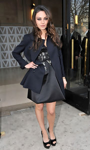 Mila wears a classic black wool coat over her satin cocktail dress for the Miu Miu fashion show in Paris.