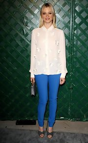 Amy Smart paired her crisp white blouse and bright blue pants with studded dark blue mules.