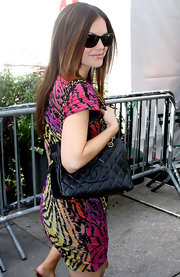Rachel is carrying a black quilted leather tote with chained straps.