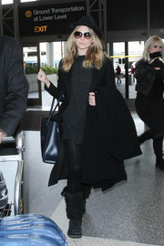 Natalie Dormer was demure in head-to-toe grey and black while sporting a wool coat over her sweater dress at LAX.