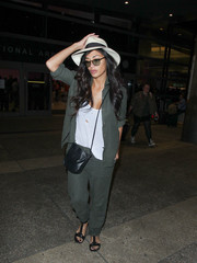 Nicole Scherzinger layered an unbuttoned moss-green shirt over a torn white tank for a flight.