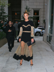Nina Agdal headed to the Fashion Media Awards wearing a black and gold mesh-panel dress by Alexander McQueen.