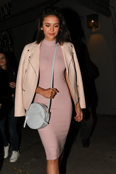 Nina Dobrev accessorized with a round leather shoulder bag by Donatienne while enjoying a night out at Craig's.