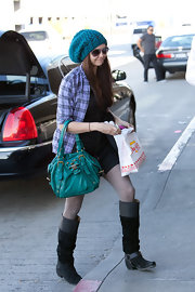 Nina wore a vibrant teal, knitted beanie to complement her matching leather handbag.