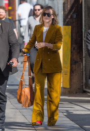 Olivia Wilde teamed her suit with a camel-colored tassel shoulder bag.