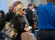 Olivia Newton-John was spotted at LAX carrying her luggage, including a roomy metallic tote.