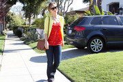 Olivia Wilde wears a sunny yellow sweater over a red tunic as she strolls through a West Hollywood neighborhood.
