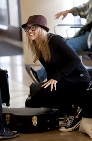 Emily travels comfortably in a pair of black converse sneakers. The actress adds a girly touch with pale pink socks.