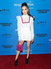 A fuchsia suede purse with gold buckle detail pulled Jenna Ortega's look together.