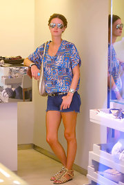 Nicky wore bold studded, gladiator sandals with blue, cutoff shorts and a printed top.