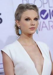 Taylor Swift added a pop of color to her white ensemble with a pair of blue Sutra  gemstone earrings.