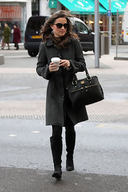 Pippa Middleton bundled up for the chilly British weather in a chic wool coat. She topped off her look with black suede knee-high boots.