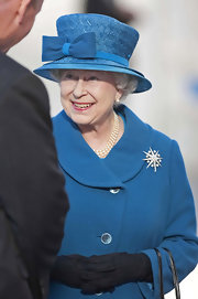 The Queen loves to wear beautiful decorative hats.  This aqua teal straw hat with a wool bow detail is just her style.