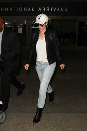 Rachel McAdams teamed black ankle boots with faded jeans and a leather jacket for an edgy airport look.