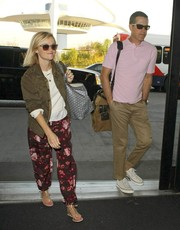 Reese Witherspoon contrasted feminine floral pants with a military-style jacket for her flight out of LAX.