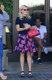 Reese Witherspoon was her usual girly self in a blue Draper James knit top with a flower-appliqued yoke while grabbing lunch.