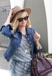 Reese Witherspoon accessorized her breezy attire with a large gold chain necklace boasting a white fish pendant.