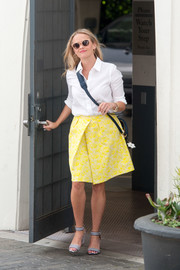 Reese Witherspoon dolled up her plain shirt with a yellow jacquard skirt by Draper James.