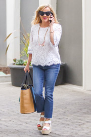 Reese Witherspoon balanced out her casual jeans with a chic white lace blouse by Draper James for a day out in LA.