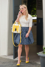 Reese Witherspoon finished off her well-coordinated attire with a yellow and white cross-body tote by Draper James.