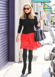 Reese Witherspoon teamed opaque tights with a red lace mini skirt for her cute cold-weather look.