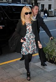 Reese Witherspoon winterized a flirty floral dress with a black coat and tights.