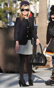 Making a classic appearance Reese stepped out in a tailored look in a grey skirt and navy blue blazer. She completed her look with a cute black leather bag.
