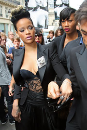Rihanna adds some shine to her lapel with this big silver brooch.