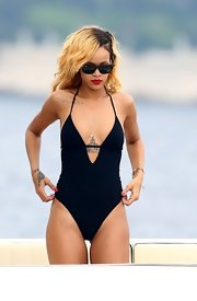 Rihanna showed off her fit figure with this solid black one-piece suit.