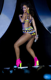 Rihanna rocked some acid green hoops along with a patterned costume and neon boots during one of her performance.