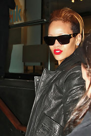 Here Rihanna is wearing a modern twist on a very classic sunglasses style - the wayfarer.  These shades are designed with a wider temple and some extra gold hardware.