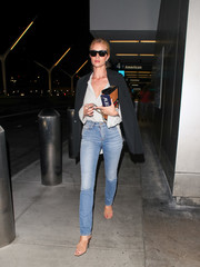 Rosie Huntington-Whiteley teamed classic blue jeans with a button-down shirt and a blazer for a flight.