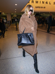 Rosie Huntington-Whiteley cut a posh figure at LAX in a camel fur coat by Max Mara layered over black leather skinnies.