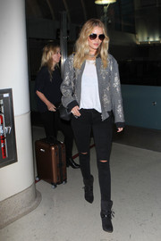Rosie Huntington-Whiteley went for a tough-glam airport look in this embellished gray bomber jacket by Dries Van Noten.