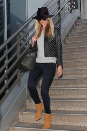 Rosie Huntington-Whiteley was edgy in slouchy camel-colored Brian Atwood boots and a studded leather jacket while catching a flight at LAX.