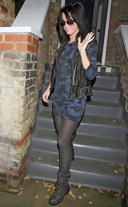 Katy's cool, chunky boots complement her trendy leather vest and long sleeve mini.