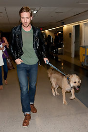 Ryan Gosling wore heavy duty camel boots as he prepared to depart LAX with his beloved pooch in tow.