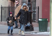 SJP walks her son James to school looking all cozied up in a black fur-hooded coat and a pair of Uggs. She adds a glamorous accessory by carrying a black leather tote.