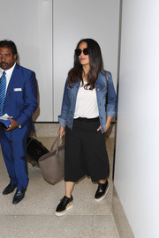 Salma Hayek kept it relaxed in an Unpublished denim jacket layered over a plain white shirt while catching a flight.