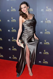 Miranda Kerr accessorized her sultry gown with metallic sandals.