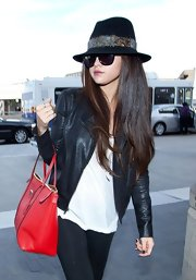 Selena Gomez showed off her high-fashion style with over-sized sunglasses and a feathered walker hat.