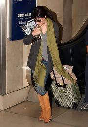 Selena shows her airport style with a long olive pashmina layered over her casual pieces.