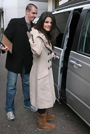 Selena covered up in a long, button down trench and a comfy pair of high top, sheepskin boots.
