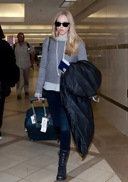 Amanda Seyfried traveled in rugged style, opting for black leather lace-up combat boots.
