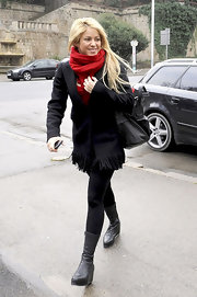 Shakira adds on some height in a pair of black wedge boots with leggings and a fringed blazer.