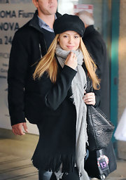 Shakira looks sweet at the airport in a black newsboy cap and warm scarf.