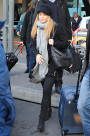 Shakira stays warm in an extra long soft gray scarf while arriving in Rome.