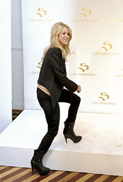 Shakira stepped on stage wearing buckled, platform boots with satin pants and a blazer.
