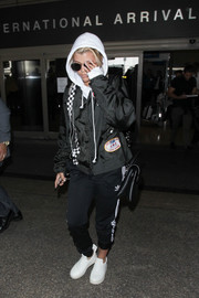 Sofia Richie tried to go incognito in a black racing jacket, a hoodie, and a pair of shades while arriving on a flight at LAX.