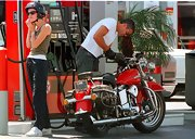 French actress Celine Balitran adjusts her motorcycle helmet while out for a ride with George Clooney.